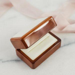 Pudełko przeznaczone na pierścionek zaręczynowy, wykonane z lakierowanego drewna. Środek ekoskóra biała.